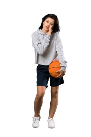 A full-length shot of a Young woman playing basketball whispering something over isolated white background Standard-Bild