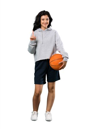 A full-length shot of a Young woman playing basketball pointing up a great idea over isolated white background