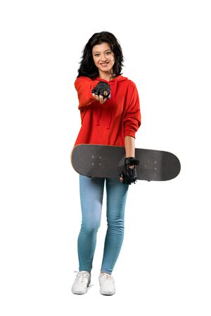 A full-length shot of a Young skater woman points finger at you with a confident expression over isolated white background 版權商用圖片 - 131778197
