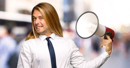 Blond businessman with long hair taking a megaphone that makes a lot of noise at outdoors Stockfoto