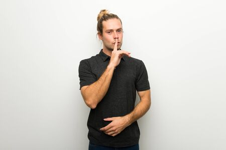 Blond man with long hair over white wall showing a sign of silence gesture putting finger in mouth