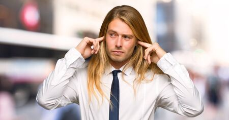 Blond businessman with long hair covering both ears with hands at outdoors