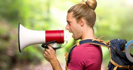 Hiker man with mountain backpacker shouting through a megaphone to announce something in lateral position in the mountain