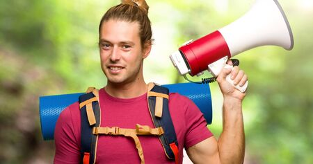 Hiker man with mountain backpacker holding a megaphone in the mountain