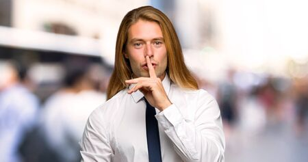 Blond businessman with long hair showing a sign of silence gesture putting finger in mouth at outdoors