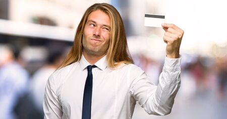 Blond businessman with long hair taking a credit card without money at outdoors
