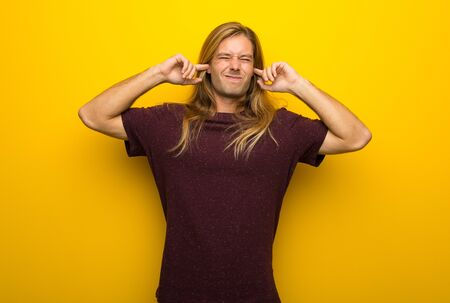 Blond man with long hair over yellow wall covering both ears with hands