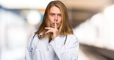 Doctor man showing a sign of silence gesture putting finger in mouth in a hospital Imagens