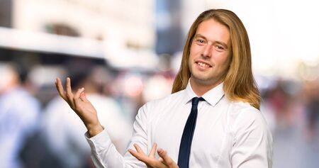 Blond businessman with long hair extending hands to the side for inviting to come at outdoors