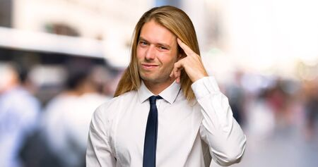 Blond businessman with long hair making the gesture of madness putting finger on the head at outdoors