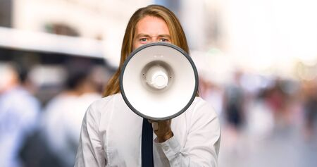 Blond businessman with long hair shouting through a megaphone to announce something at outdoors