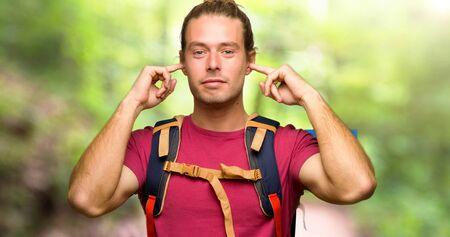 Hiker man with mountain backpacker covering both ears with hands in the mountain