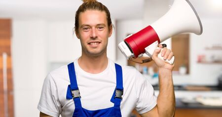 Workman holding a megaphone in a house