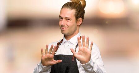 Peluquero con delantal está un poco nervioso y asustado estirando las manos hacia el frente en una peluquería