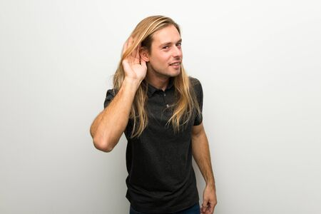 Blond man with long hair over white wall listening to something by putting hand on the ear