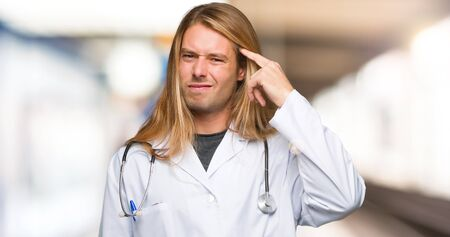 Doctor man making the gesture of madness putting finger on the head in a hospital Imagens