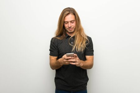 Blond man with long hair over white wall sending a message with the mobile