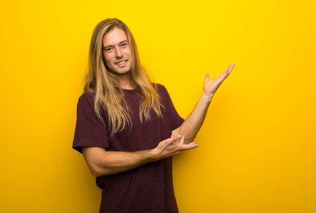 Blond man with long hair over yellow wall extending hands to the side for inviting to come Reklamní fotografie - 131342495