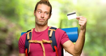 Hiker man with mountain backpacker taking a credit card without money in the mountain Stok Fotoğraf
