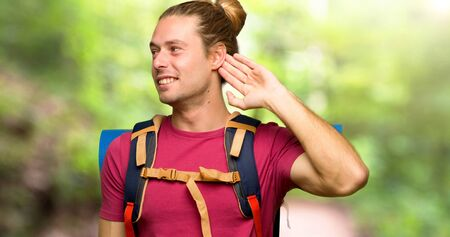Hiker man with mountain backpacker listening to something by putting hand on the ear in the mountain