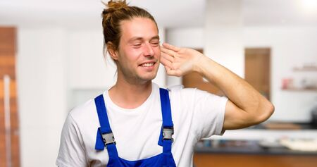 Workman listening to something by putting hand on the ear in a house Imagens