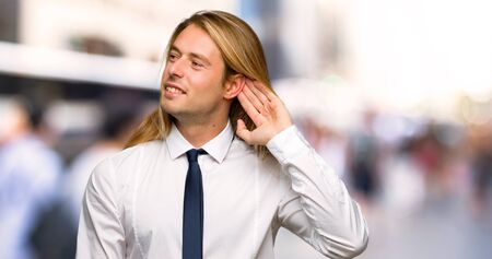 Blond businessman with long hair listening to something by putting hand on the ear at outdoors