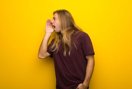Blond man with long hair over yellow wall shouting with mouth wide open to the lateral Stok Fotoğraf