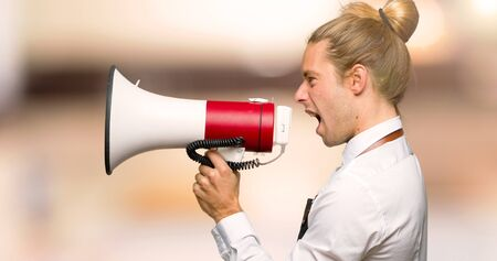 Barber man in an apron shouting through a megaphone to announce something in lateral position in a barber shop