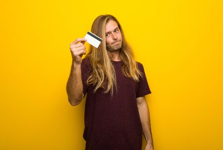 Blond man with long hair over yellow wall taking a credit card without money