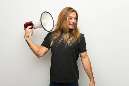 Blond man with long hair over white wall taking a megaphone that makes a lot of noise