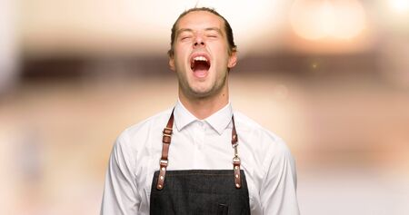 Barber man in an apron shouting to the front with mouth wide open in a barber shop