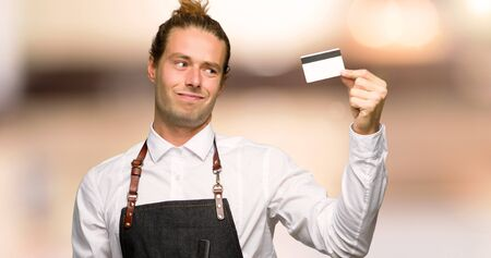 Barber man in an apron taking a credit card without money in a barber shop