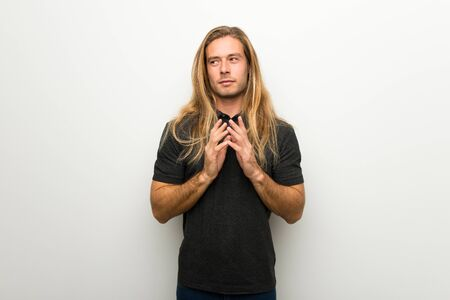 Blond man with long hair over white wall scheming something