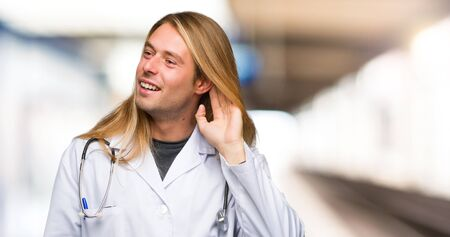 Doctor man listening to something by putting hand on the ear in a hospital