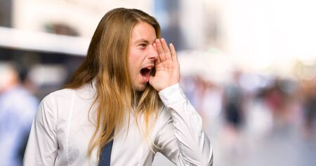 Blond businessman with long hair shouting with mouth wide open to the lateral at outdoors