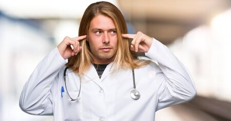 Doctor man covering both ears with hands in a hospital