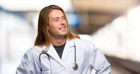 Doctor man posing with arms at hip and laughing in a hospital
