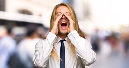 Blond businessman with long hair shouting and announcing something at outdoors Stok Fotoğraf
