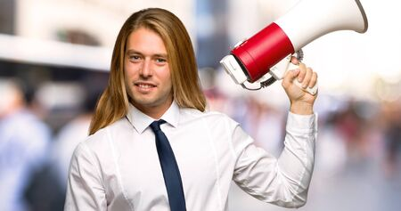 Blond businessman with long hair holding a megaphone at outdoors