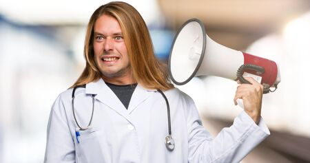 Doctor man taking a megaphone that makes a lot of noise in a hospital
