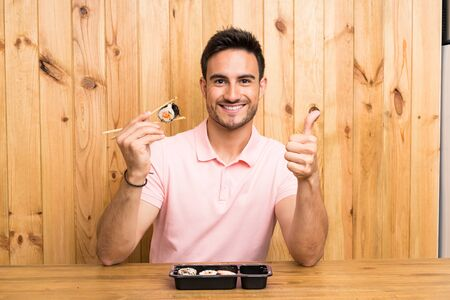 Handsome young man in a kitchen with sushi Stockfoto