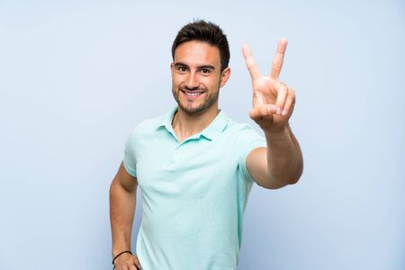 Handsome young man over isolated background smiling and showing victory sign