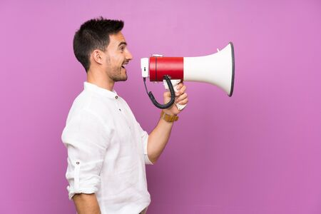 Handsome young man over isolated background shouting through a megaphone