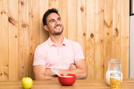 Handsome young man in a kitchen having breakfast looking up while smiling