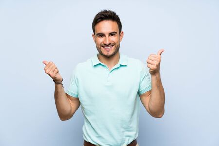 Handsome young man over isolated background with thumbs up gesture and smiling