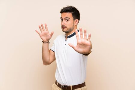 Handsome young man over isolated background nervous stretching hands to the front