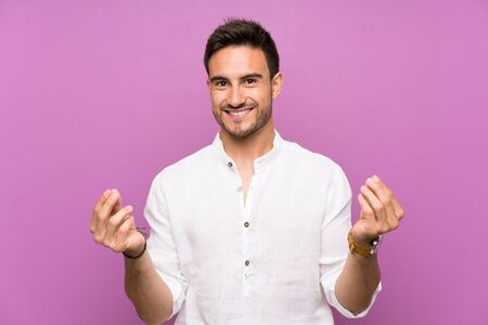 Handsome young man over isolated background making money gesture