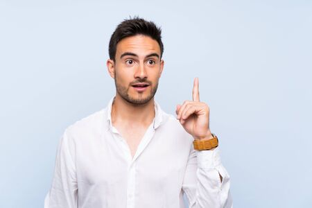 Handsome young man over isolated blue background thinking an idea pointing the finger up