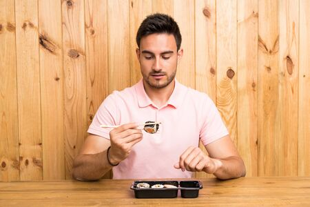 Handsome young man in a kitchen with sushi Stock Photo - 131366004