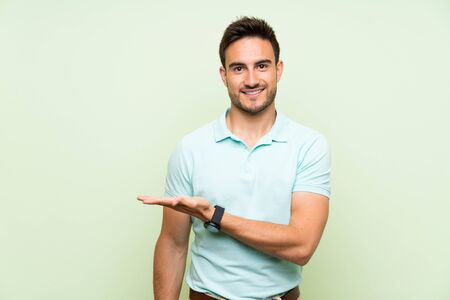 Handsome young man over isolated background presenting an idea while looking smiling towards Stockfoto